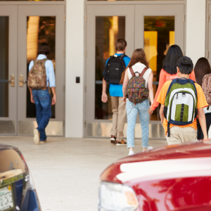 High school students walk into their school building during the springtime.