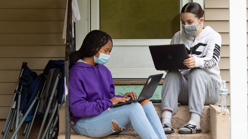 Two girls who are college students sit on their front porch with face masks on. They are doing homework on their laptops.