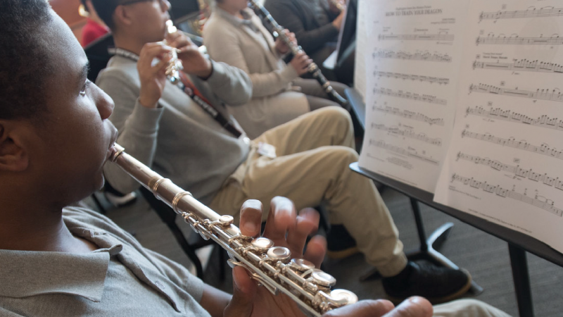 A high school student plays flute with his classmates during music class.