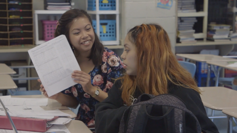 Two female students interact